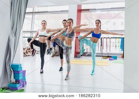 Group of slim Caucasian girls standing in one-leg stance during workout class in gym.