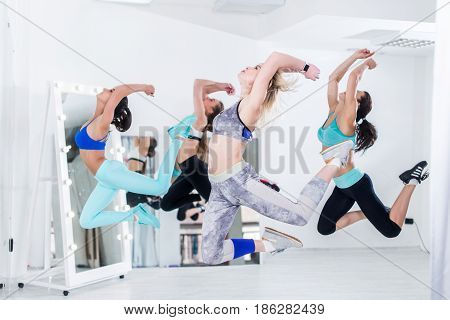 A group of slim fit athletic young women doing simultaneous jump in dancing studio.