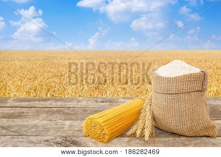 uncooked spaghetti from durum wheat, wholegrain flour in bag on table with ripe cereal field on the background. Golden wheat field with blue sky. Healthy food