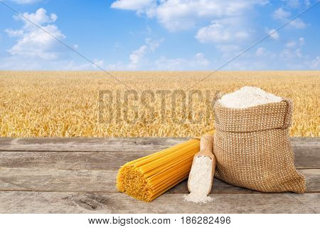 uncooked spaghetti from durum wheat, wholegrain flour in bag and scoop on table with ripe cereal field on the background. Golden wheat field with blue sky. Photo with place for text