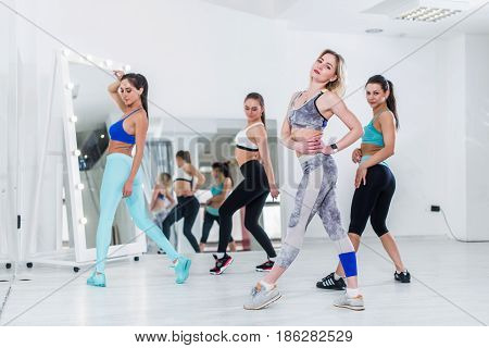Female dance team wearing sports bra and leggings posing in studio standing backside and sideways turning to camera.