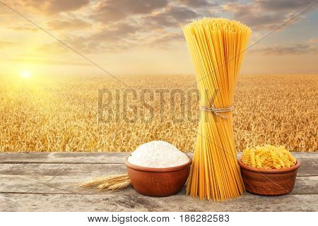 uncooked pasta from durum wheat, wholemeal flour in bowl on table with ripe cereal field on the background. Golden wheat field on sunset. Photo with place for text