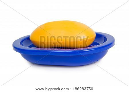 Soap of yellow color in a dark blue soap tray is isolated on a white background