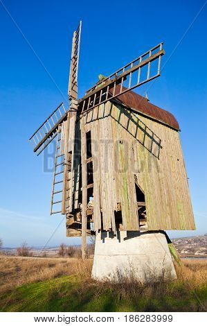 Wooden old windmill on the blue sky background