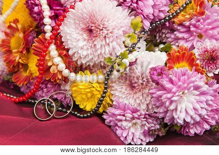 Colorful chrysanthemum and daisy flowers on a claret fabric with wedding rings and a beads