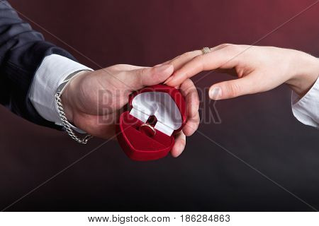 Man gives a gold engagement ring to woman in a red box