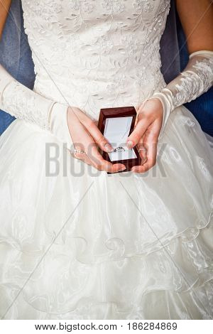 Bride looks at box with engagement ring