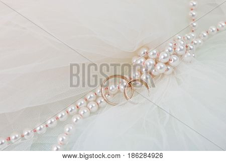 Wedding rings and a pearl necklace close up