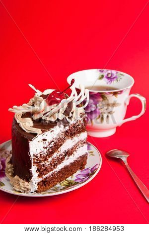 chocolate cake with tea on the red background