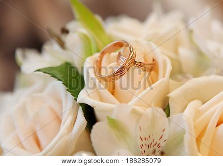 Wedding rings are lying on wedding bouquet