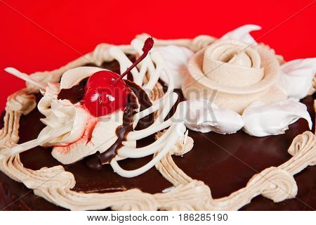 Close up chocolate cake with cream and cherry on the red background