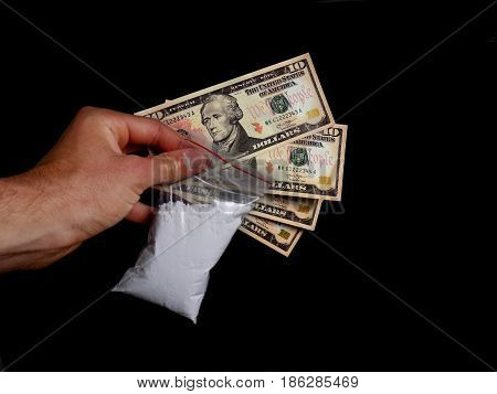 Drug dealer holding cocaine drug powder bag and dollar money bills, men selling drugs junkie