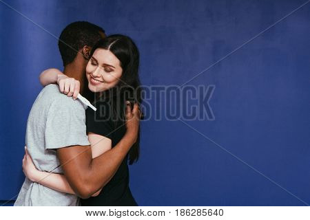 Pregnancy test, positive result. Happy couple hug, future interracial parents excited about good news. Happiness, joy, togetherness, success in vitro fertilization concept.