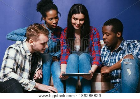 Company of young interracial friends have fun with tablet. International friendship and home leisure, social network, movie and education concept. Four people look at the tablet with interest.