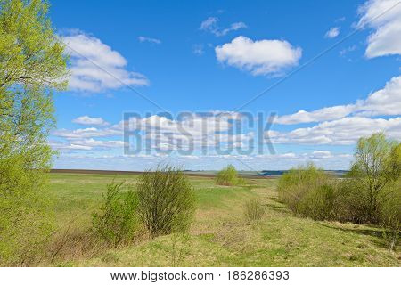 Spring landscape with fields ravines and blue sky with clouds