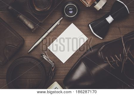 brown shoes, belt, and film camera on wooden background. men's accessories on the table. above view on men's accessories. brown leather men's accessories. men's accessories concept.