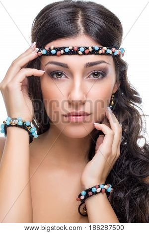 Beautiful blond young woman with black headband and bracelets with jems. Beauty shot on white background. Isolated. Copy space.
