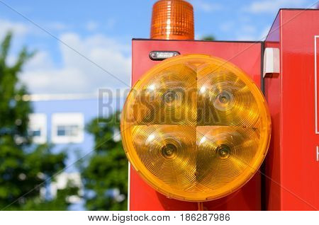 Orange lens on a large round lamp attached to a red metal rectangular machine with revolving warning light on top in a close up view