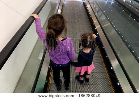 Two sister holds hands on moving walkway. Real people. copy space