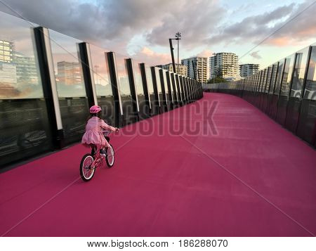 Young Girl Ride A Bike On  Bright Pink Cycleway In Auckland New Zealand