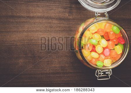 glass jar full of colorful sweets on the wooden table