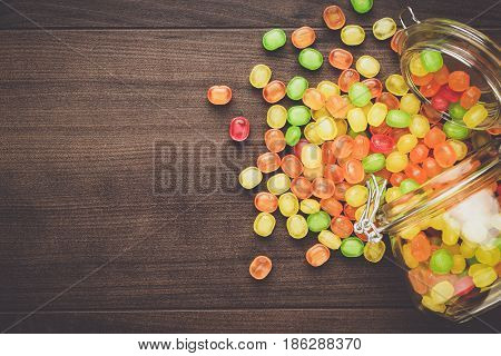 toppled over glass jar full of colorful sweets. jar of sweets on the brown table. top view of topped jar of sweets. jar of sweets on wooden background. overturned jar of sweets background with copy space