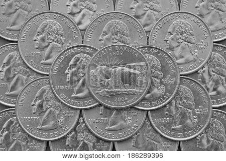 North Dakota State and coins of USA. Pile of the US quarter coins with George Washington and on the top a quarter of North Dakota State.