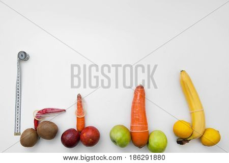 Penis measure, man power and potency, size. Four phallus with strong erection in condoms with tape on white background.