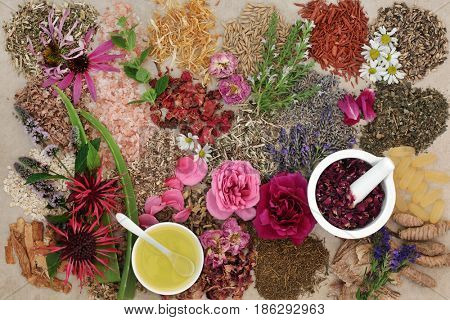 Ingredients for skin care treatment with flower and herb selection, almond oil and rose petals in a mortar with pestle on hemp background.