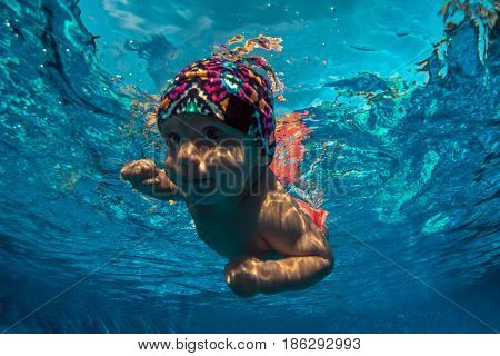 Funny photo of active baby diving in swimming pool with fun jump deep down underwater.