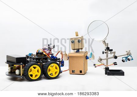 Two robots and parts for assembling a robot on a white background