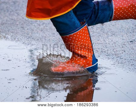 Little girl running in the rain orange shoes in the water