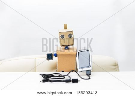 The robot holds a solar battery in its hand with a wire in the other hand a small solar battery