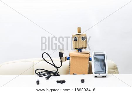 Robot holds a solar battery in his hand in the other hand a wire for a solar battery