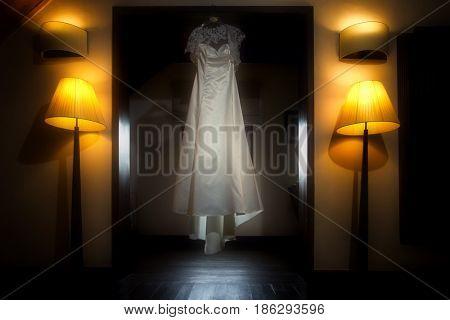Beautiful wedding dress hanging in the bride's room in darkness