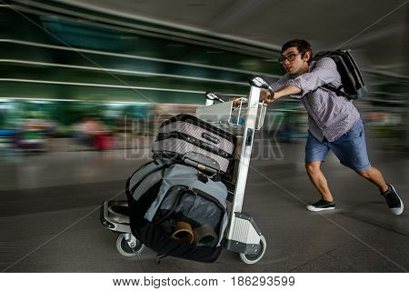 Cute boy running with suitcases at airport.