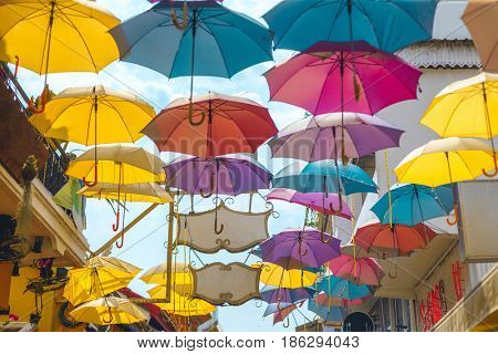 Palette of happiness. Colorful umbrellas background. Colourful umbrellas urban street decoration. Hanging Multicoloured umbrellas over blue sky. Bright Colors backdrop.