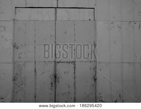 Background of large metallic light gray sheets joined together in which the doors and gates are imperceptibly inscribed