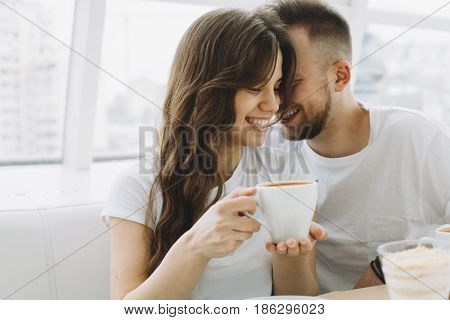 Attractive young couple on a date in a cafe. Beautiful smiling girl trying to drink some coffee while her boyfriend is telling something in her ears. Close up