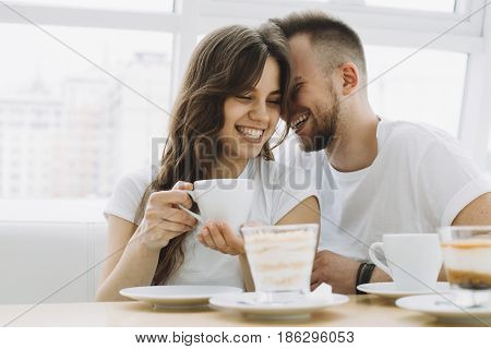 Attractive young couple on a date in a restaurant. Handsome guy is trying to say something in his girlfriend's ears or to kiss her in a cheek. Close up