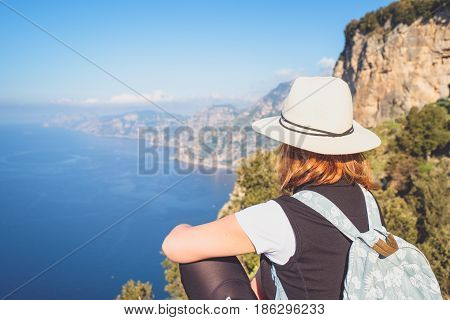 Young woman admiring a beatuful landscape view of Amalfi coast Italy