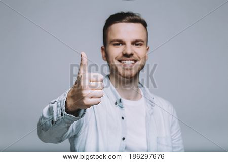 Smiling happy young man with beard in a white jeans shirt showing his thumb up right in front of the camera. Close up. Isolated