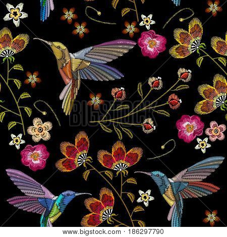 Humming bird and tropical flowers embroidery seamless pattern. Beautiful hummingbirds and exotic flowers embroidery on black background. Template for clothes textiles t-shirt design