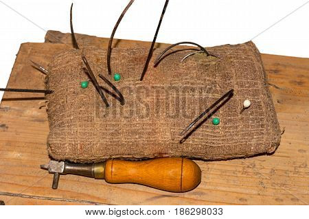 Shoemaker tool accessories sewing needle scissors and thread on linen cushion.