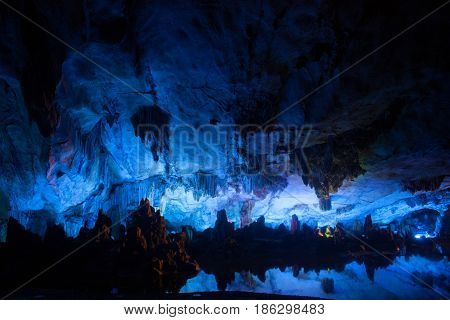 Vast cave with multicolored lighting & guided tours featuring diverse stalagmites & stalactites