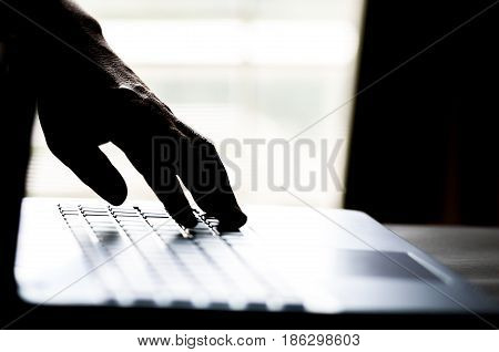 A hand reaching out through a laptop computer and signifying a cybercrime in internet theft while using online Payment Security Concept. Hacked in Black
