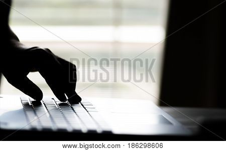 A hand reaching out through a laptop computer and signifying a cybercrime in internet theft while using online Payment Security Concept. anonymous Hacked in Black poster
