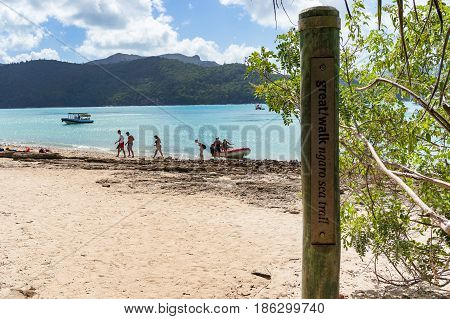 Queensland Australia - February 5 2017: Ngaro sea trail walk sign with tropical beach coastline and people in the distance. Whitsundays Australia