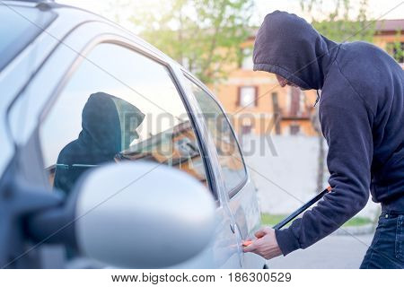 Thief trying to pick the lock of a parked car