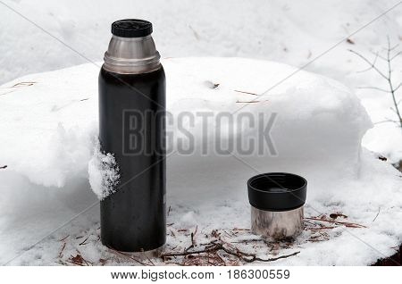 Thermos with open cup on the stump covered with snow. Winter photography